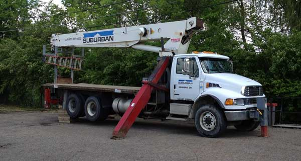 repairs and crane inspections being done on crane truck by service mechanics technians